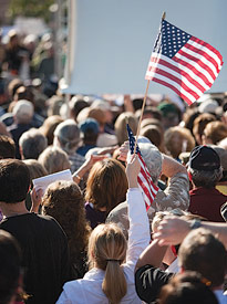 Picture of a woman holding an American flag at a rally