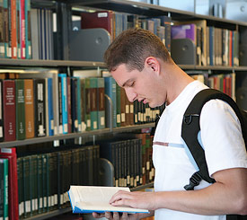 Student reading a book in a library